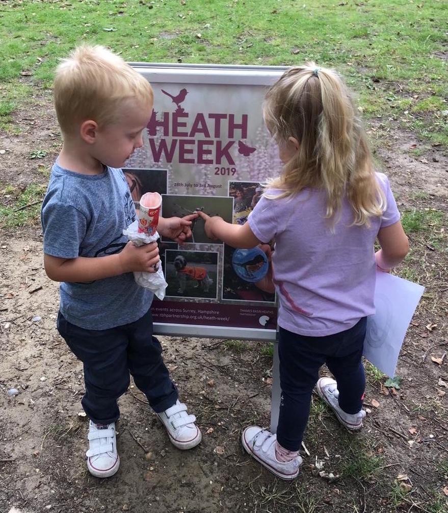 Kids looking at a Heath Week sign