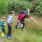 Photograph of Warden Andi pointing out a butterfly yo two attentive children