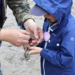 Member of ARC team helping a small child hold a smooth snake.